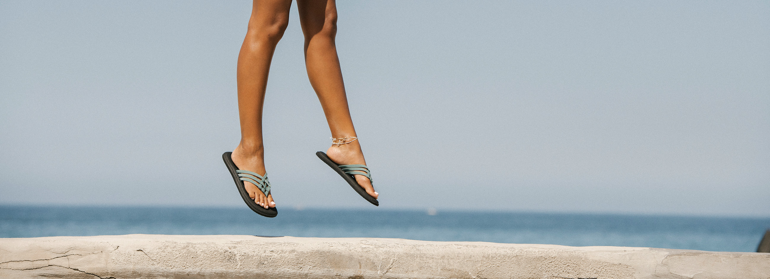 Girl jumping on concrete at the beach wearing Sanuk flip flops.
