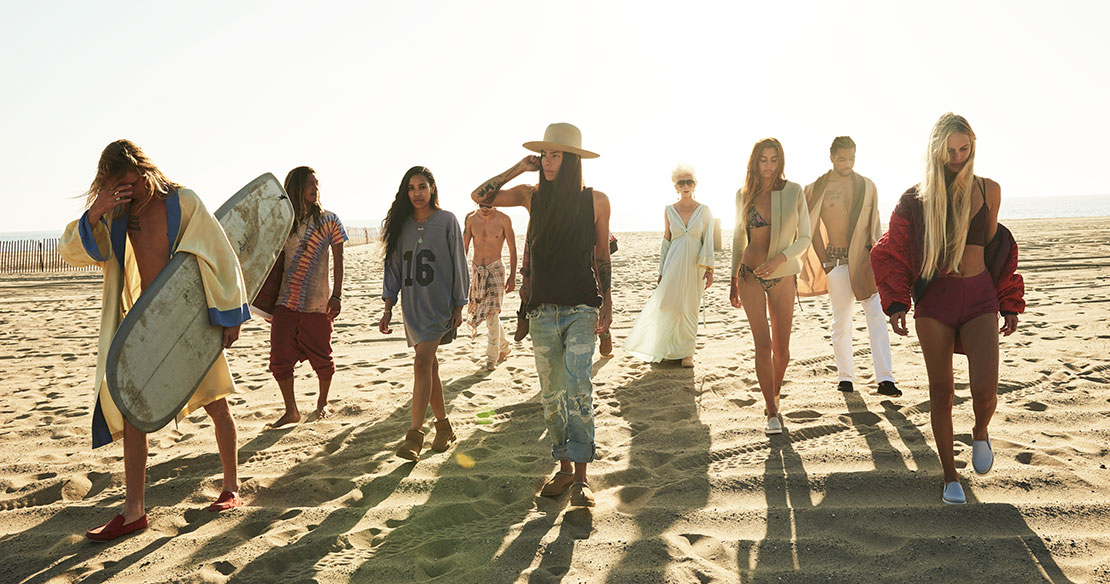 Large group walking on beach in UGG shoes.