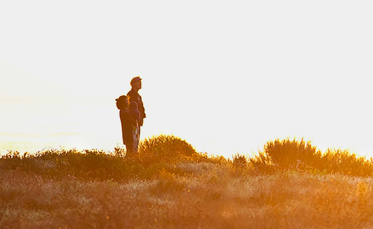 Hiker standing on ridge looking at sunset.