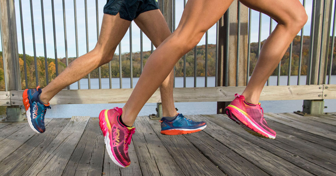 Two runners wearing Hoka One One shoes running on a pier.