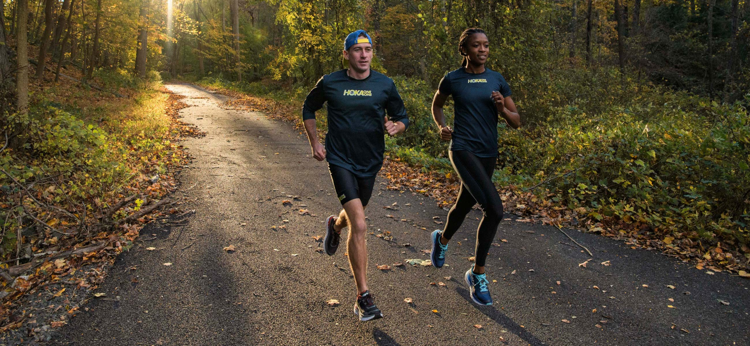 10de450ae4f9c Runners wearing Hoka One One running shoes on a trail in the woods.