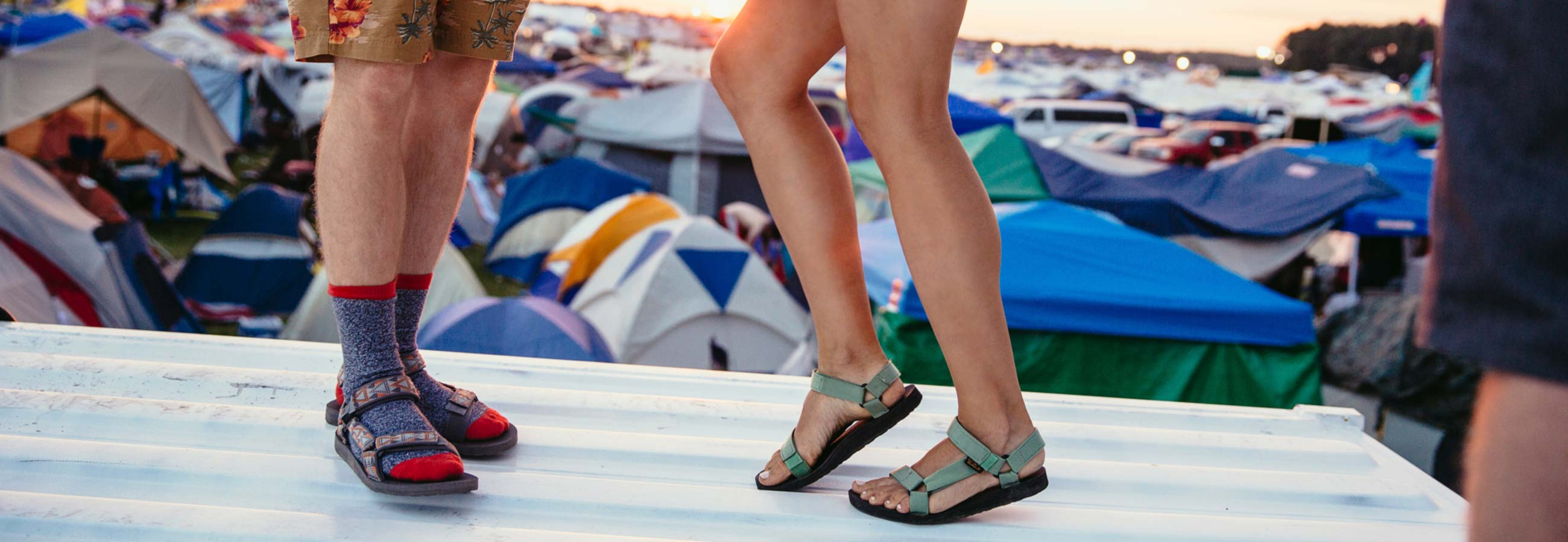 Two pairs of Teva-clad feet dancing on a platform overlooking a sea of tents.