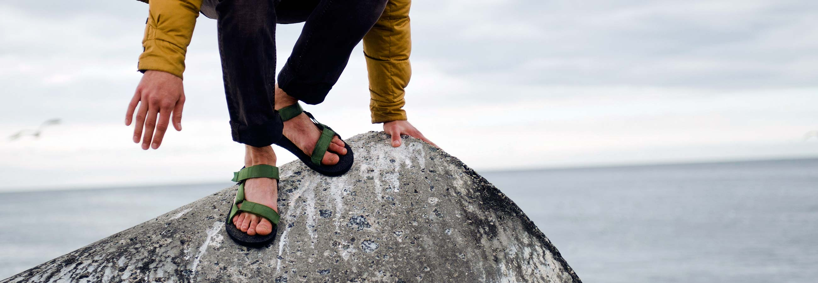 Lower half of person wearing Teva sandals climbing down a boulder overlooking the ocean.