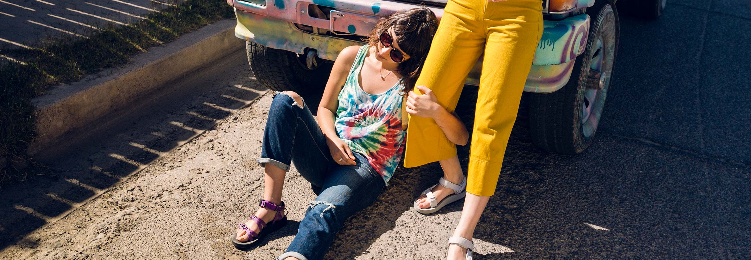 Two women leaning against a car wearing Teva sandals.
