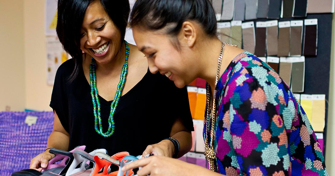 Two women smiling and working together while reviewing at shoe materials.