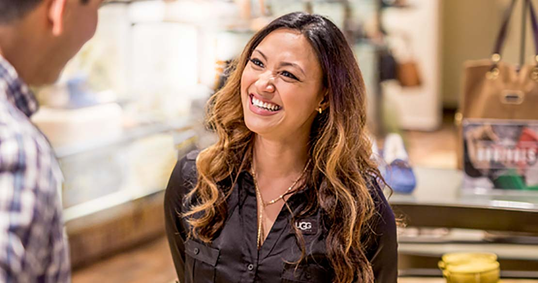 A smiling woman standing in an UGG brand retail store.