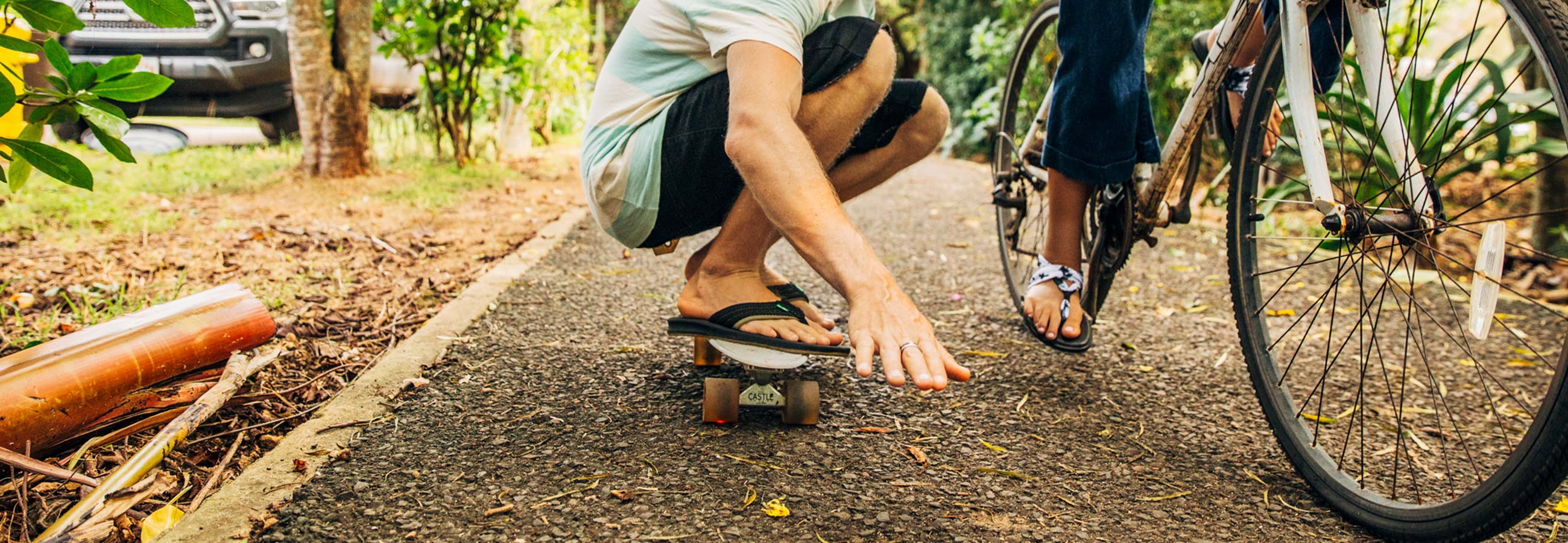 Ground level view of a man crouched low riding a skateboard next to a female riding a bicycle.