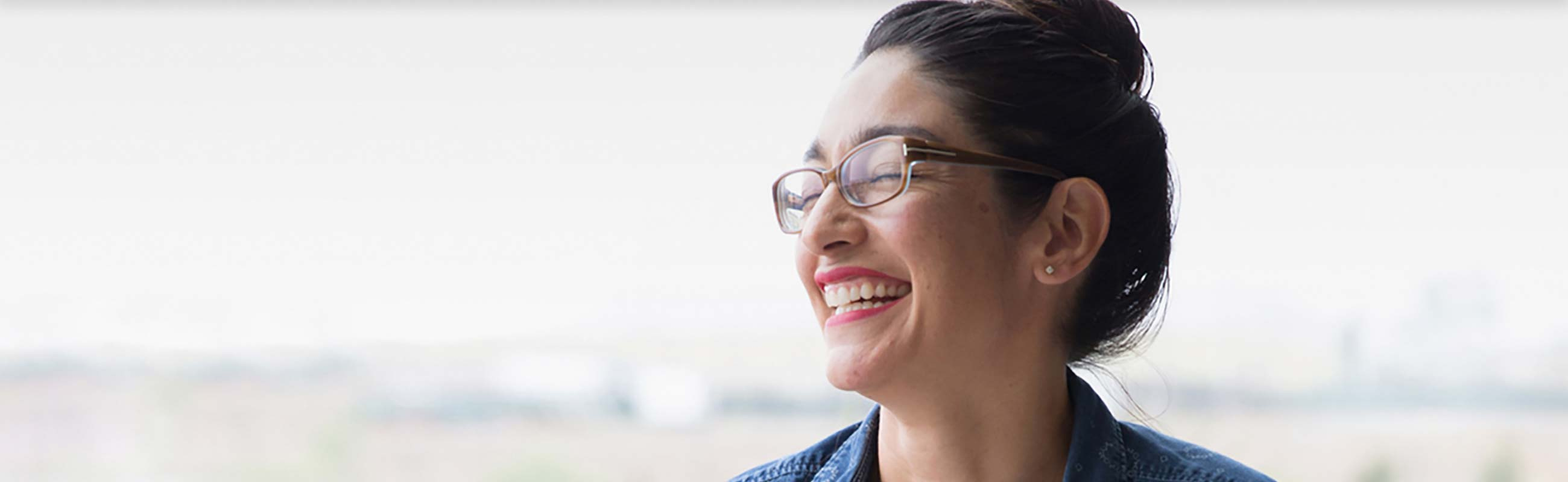 Headshot of woman wearing glasses laughing.