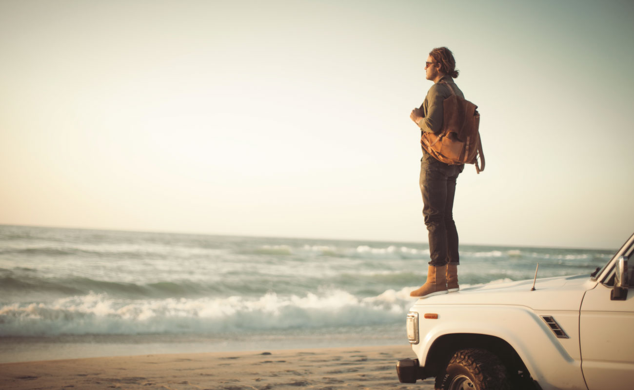 Man standing on top of car at beach