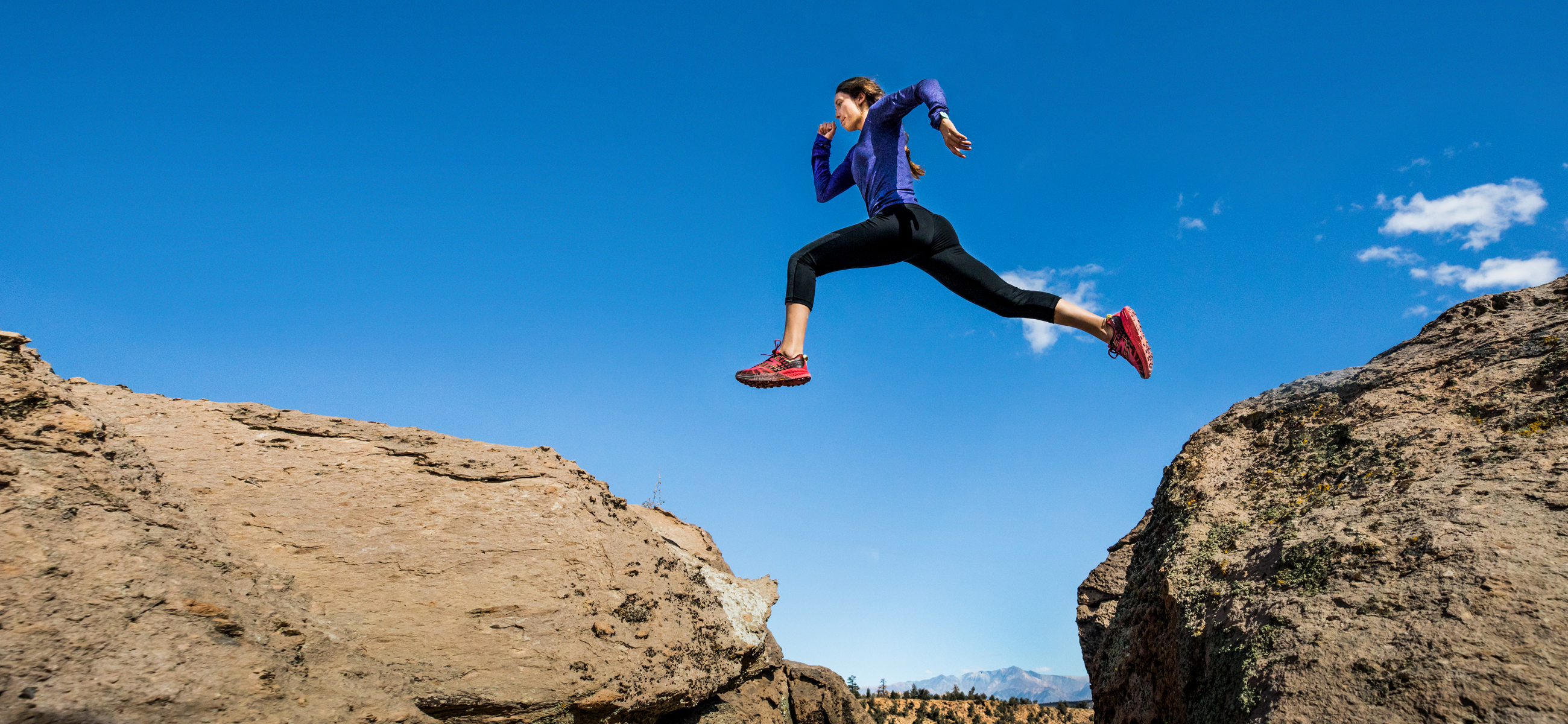 female trail runner wearing hoka one one shoes leaping over rocks