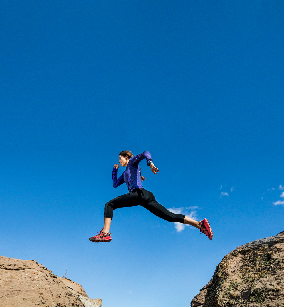 Female trail runner wearing Hoka One One shoes leaping over rocks.